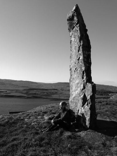 Woman Sitting By Rock Formation At Isle Of Skye Against Clear Sky