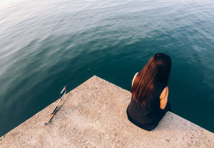 Beauty In Nature By The Sea Cinematography Day Girl High Angle View Leisure Activity Lifestyles Minimalism Nature One Person Outdoors Real People Rear View Relaxing Sea Sitting Standing Triangle Water Water_collection Women Working Young Adult Young Women