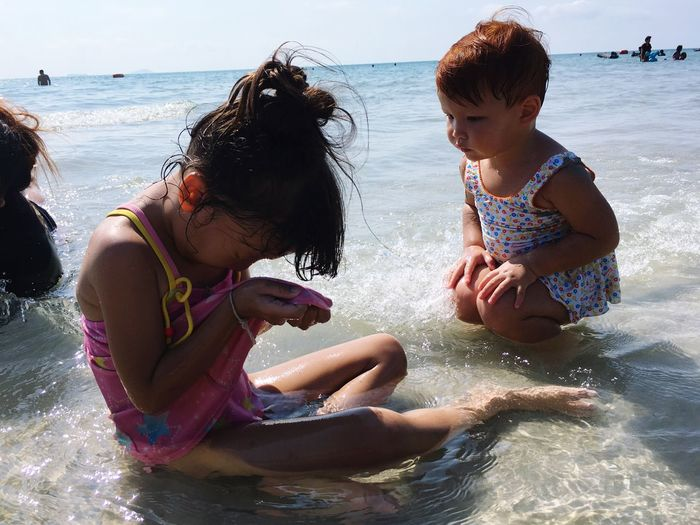 Girl with sister sitting at beach