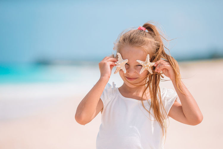 Full length of girl on beach against sky