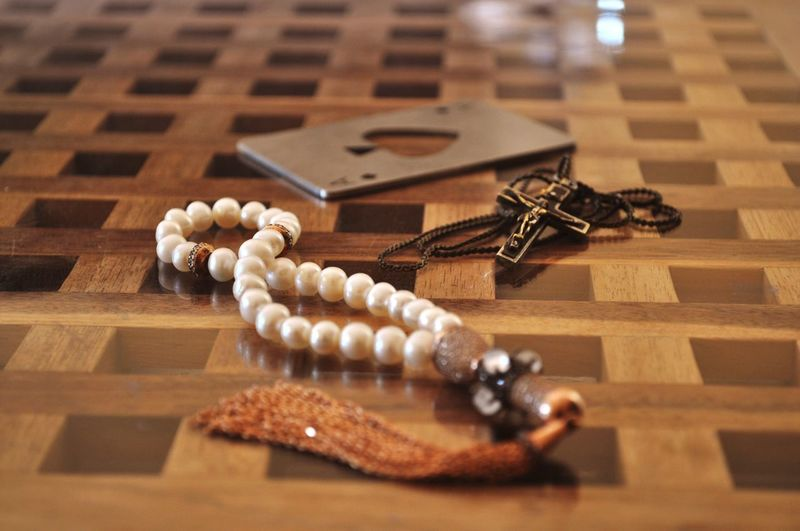 Close-Up Of Tasbih And Rosary On Floor