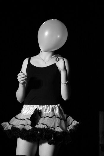 Woman With Balloon Against Black Background