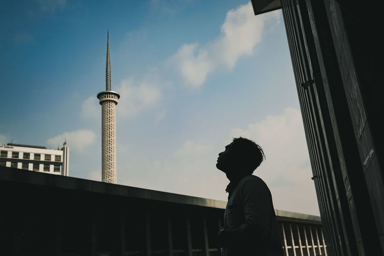Low angle view of man standing by building against sky
