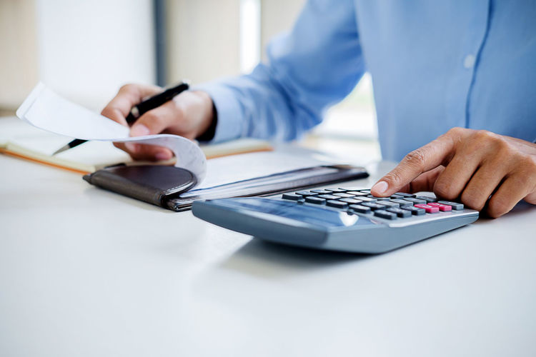 Midsection of businessman doing calculation in office