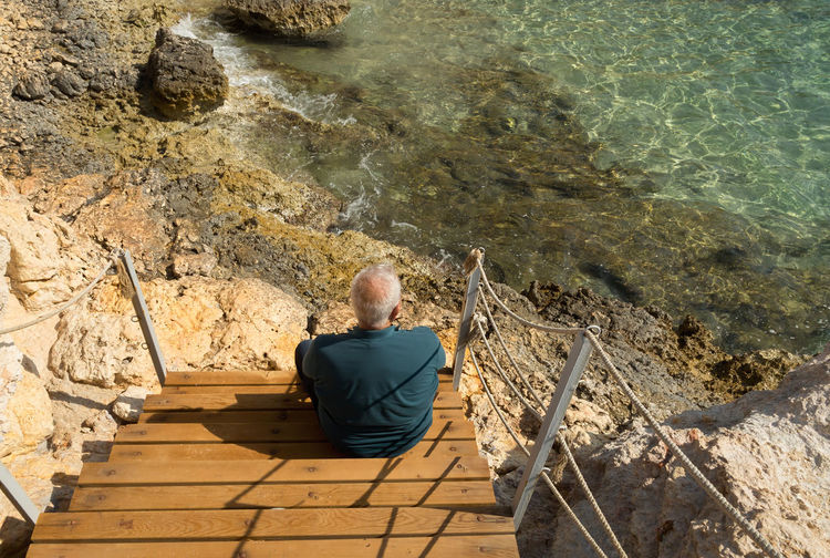 High Angle View Of Man Sitting On Steps At Shore
