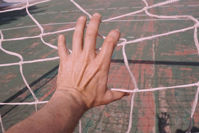 Close-up of hand holding sports net