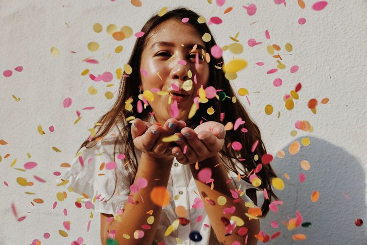 Young Woman Blowing Confetti Against Wall