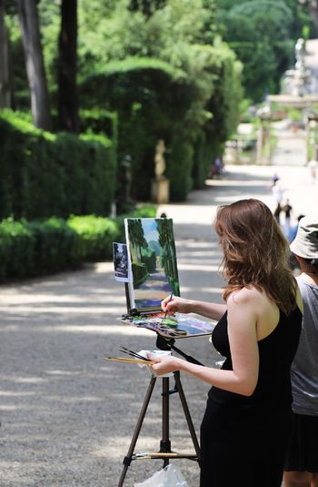 Rear view of woman painting while standing on footpath at park