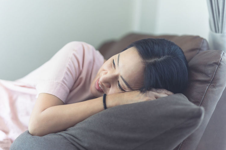 Woman lying down on bed at home