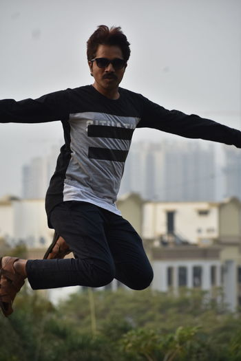 Full length of young man jumping outdoors