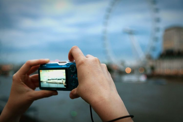 Cropped image of hands photographing millennium wheel