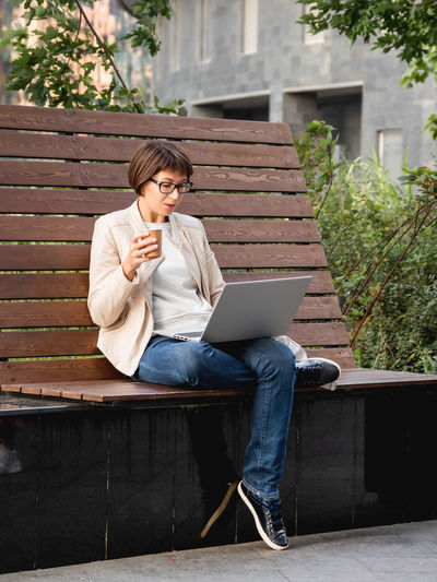 Freelance business woman sits in park with laptop. urban lifestyle of millennials. working remotely.