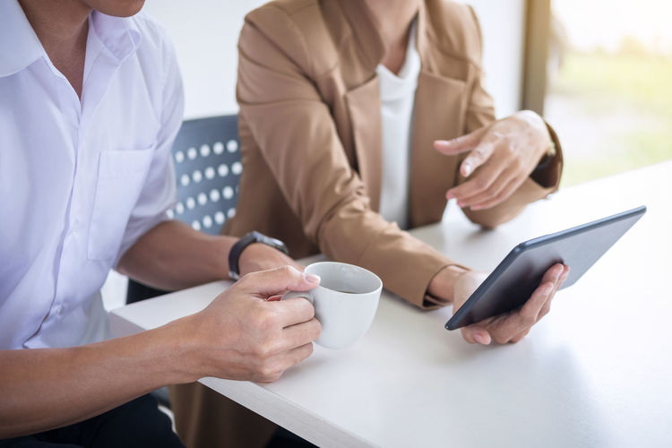 Midsection Of Man With Coffee By Colleague Using Digital Tablet On Desk