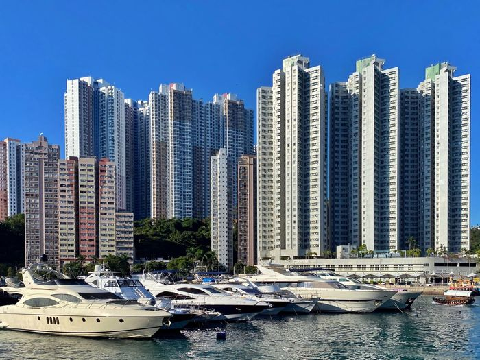 Sailboats moored in city by buildings against clear sky