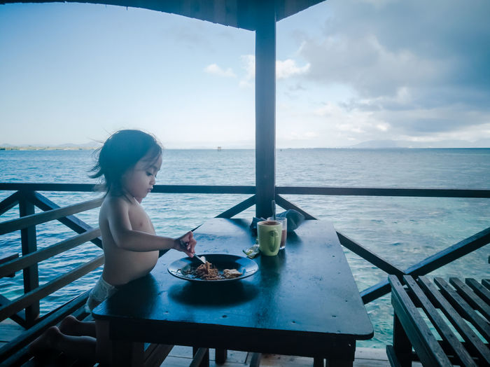 Girl sitting on table by sea against sky