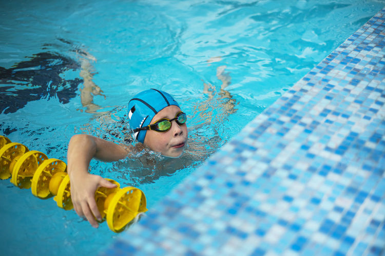 Boy in the pool. the face of a boy in swimming goggles and a swimming cap.