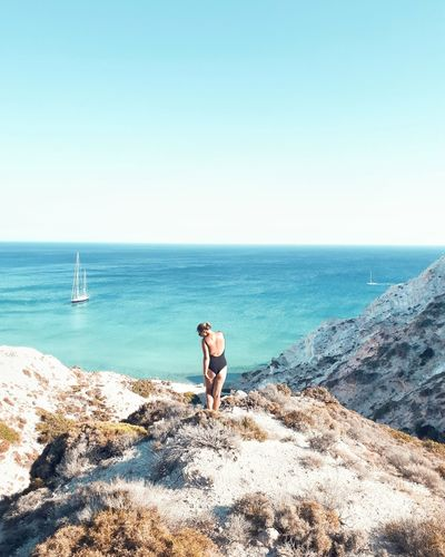 Woman standing on rock while looking at sea against clear sky