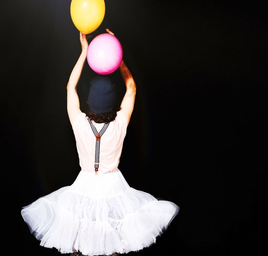Rear view of woman wearing tutu with balloons against black background