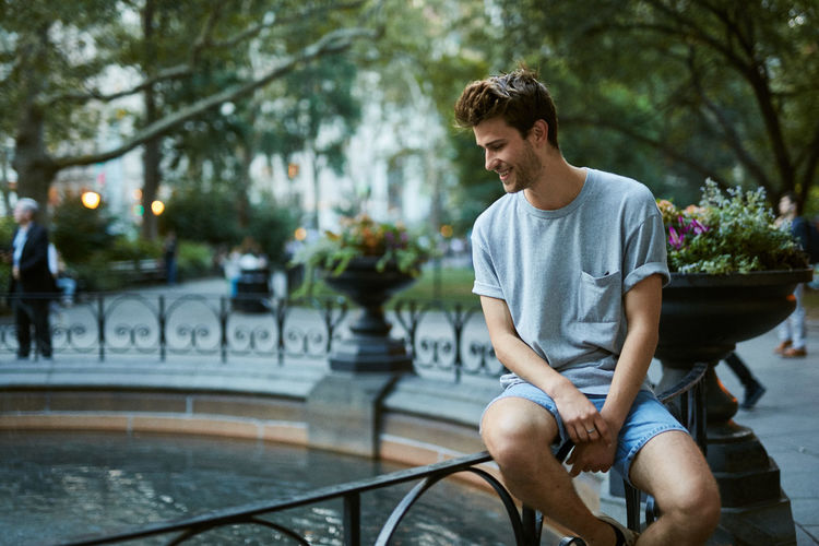 Young man sitting on bicycle in city