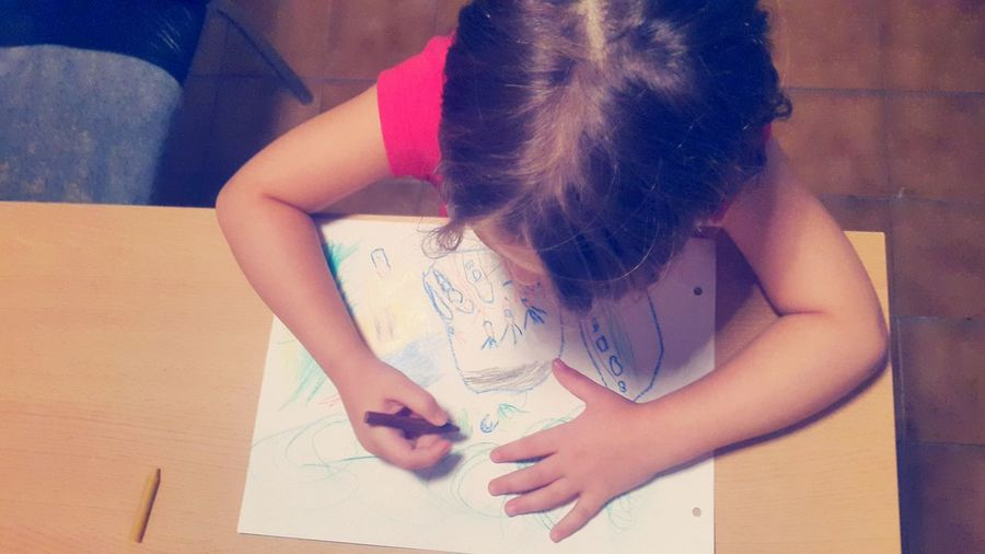 High angle view of girl drawing on paper at table