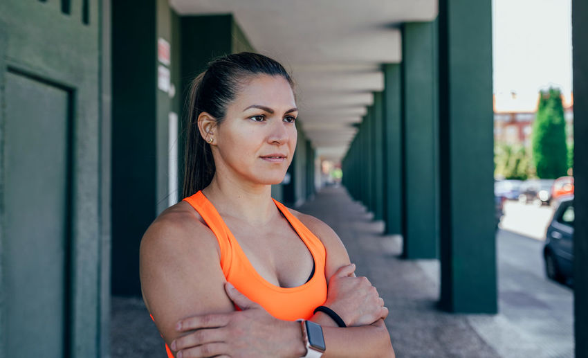 Thoughtful female athlete standing in corridor
