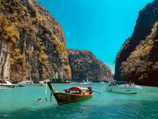 Phi Phi island, Phuket Thailand Summer Travel Thailand Dive Beach Holiday Backgrounds Hotel And Resort Boat Tourism Island Snorkeling Sea Water Nautical Vessel Transportation Sea Mode Of Transportation Sky Scenics - Nature Beauty In Nature Incidental People Rock Formation Day Tranquil Scene Blue Plant Land Tree