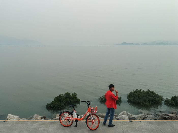 Shenzhen, China 2019 Streetphotography Iphone6s VSCO IPhoneography Mobilephotography Street Of China Water Bicycle Transportation Sea Real People One Person Lifestyles Leisure Activity Rear View Mode Of Transportation Sky Nature Horizon Over Water Beach