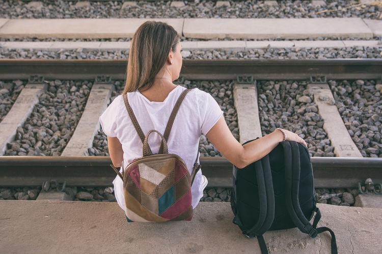 Woman sitting on railroad track
