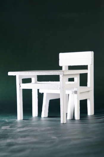 Figurine Of Chair And Table On Blackboard