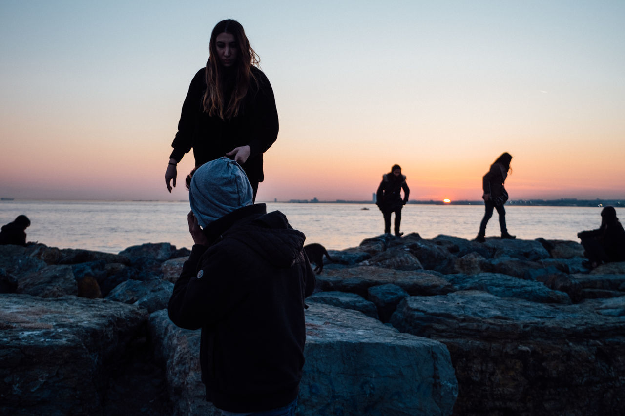 sea, rock - object, sunset, beach, horizon over water, real people, standing, nature, water, beauty in nature, sky, leisure activity, lifestyles, men, outdoors, women, vacations, togetherness, scenics, full length, clear sky, wave, friendship, day, people