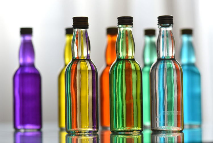 Bottle Container Glass - Material No People Transparent Multi Colored Indoors  Group Of Objects Food And Drink Choice Drink Refreshment Alcohol Variation Close-up In A Row Glass Empty Drinking Glass Hard Liquor Purity Small Group Of Objects