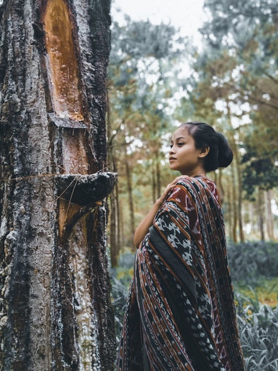 Side view of young woman looking at tree trunk