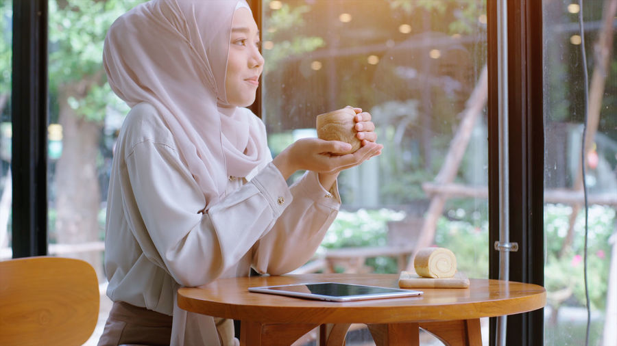 Smiling woman in hijab sitting at cafe