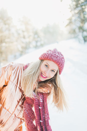 Portrait of smiling woman in warm clothing standing on snow