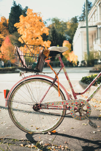 Bicycle with flat wheel and painted with hearts in the city on a sunny autumn day.