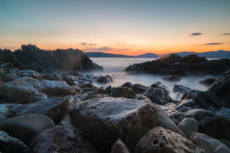 Scenic view of rocky shore against sky during sunset