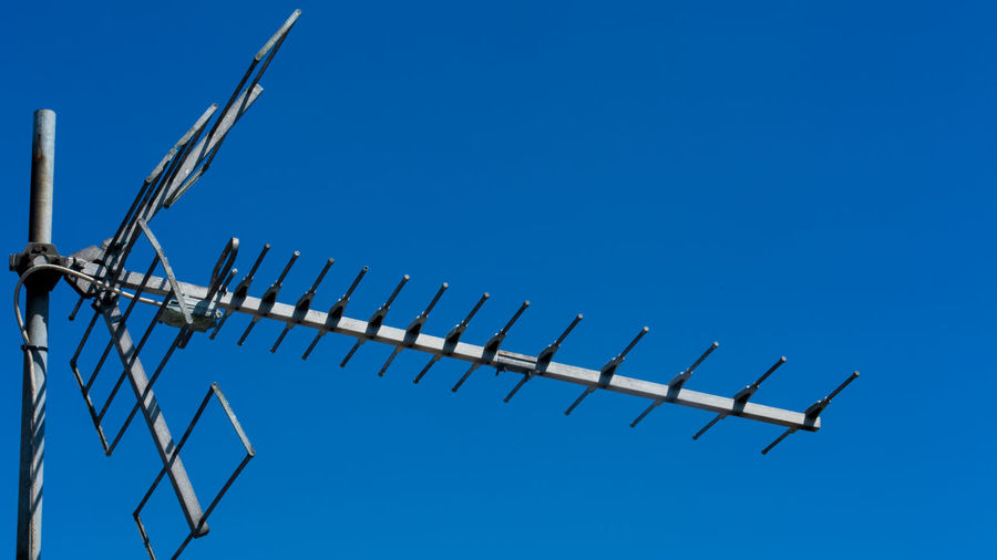Low angle view of antenna tv against clear blue sky