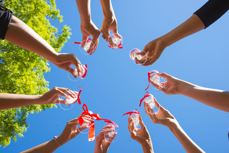 Cropped Hands Of Friends Toasting Drinks Against Clear Blue Sky