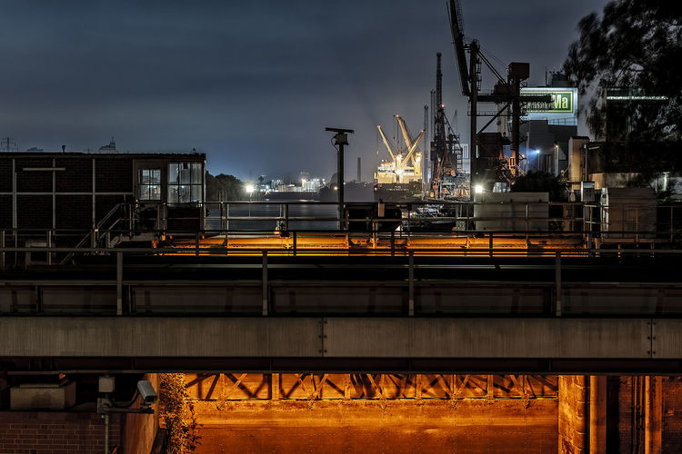 Industrial Buildings Against Cloudy Sky At Night