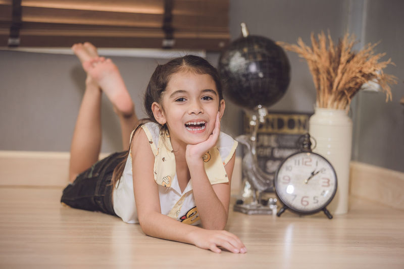 Full length portrait of cute cheerful girl lying on floor at home