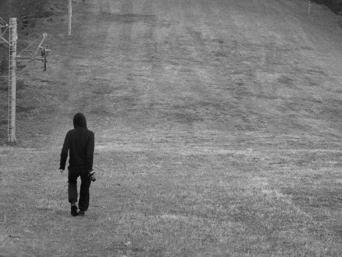 Rear view of hooded man walking on field