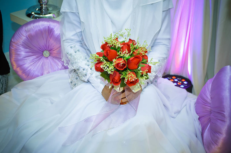 Midsection of bride holding artificial rose bouquet during wedding ceremony