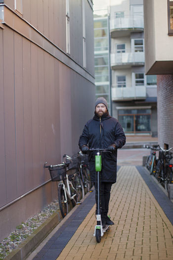 Full length of man standing on railing in city