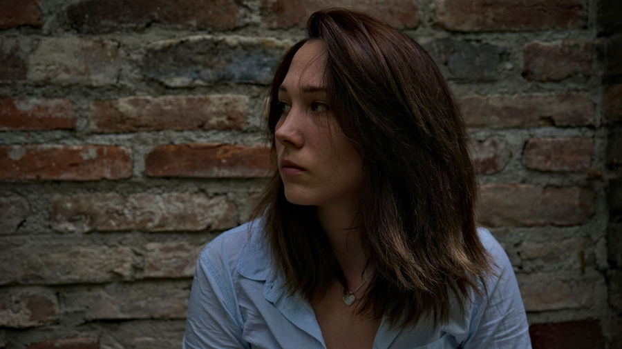 Close-up of thoughtful young woman looking away while standing against brick wall