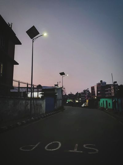 Street lights against sky in city at dusk