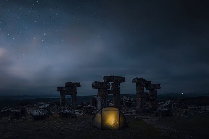Tent by abandoned built structure against sky at night