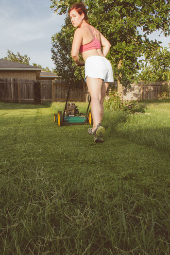 Full length of woman with lawn mover in yard