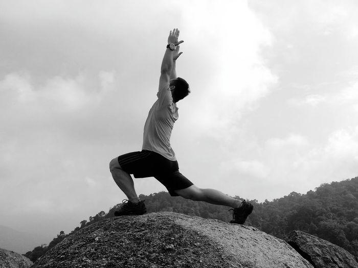 Full length of man practicing yoga on rock against sky