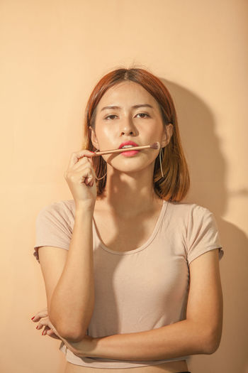 Portrait of young woman with make-up brush standing against wall