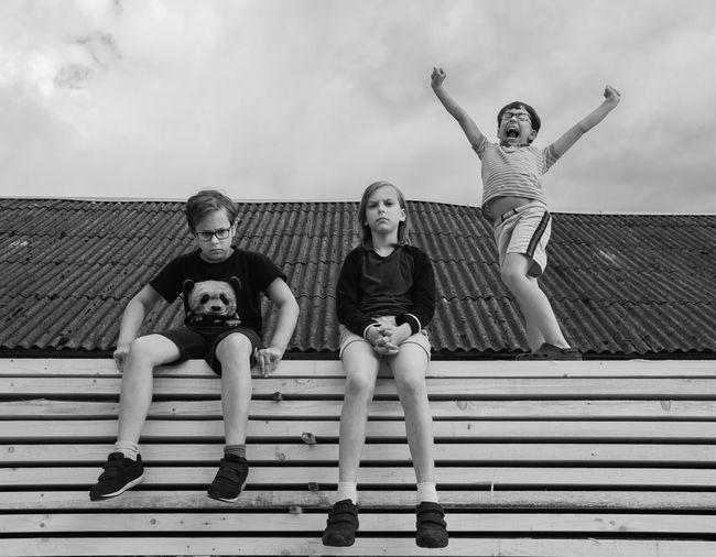 Portrait of friends sitting against sky